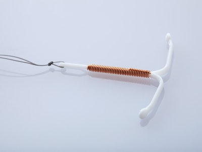 A copper IUD on a white background. Here are 8 signs that your IUD has moved