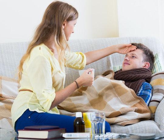 woman checks the forehead of a sick man