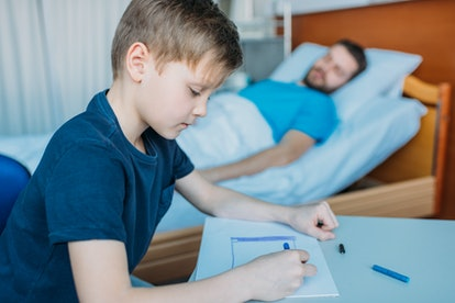 young boy writes note while father lies in bed
