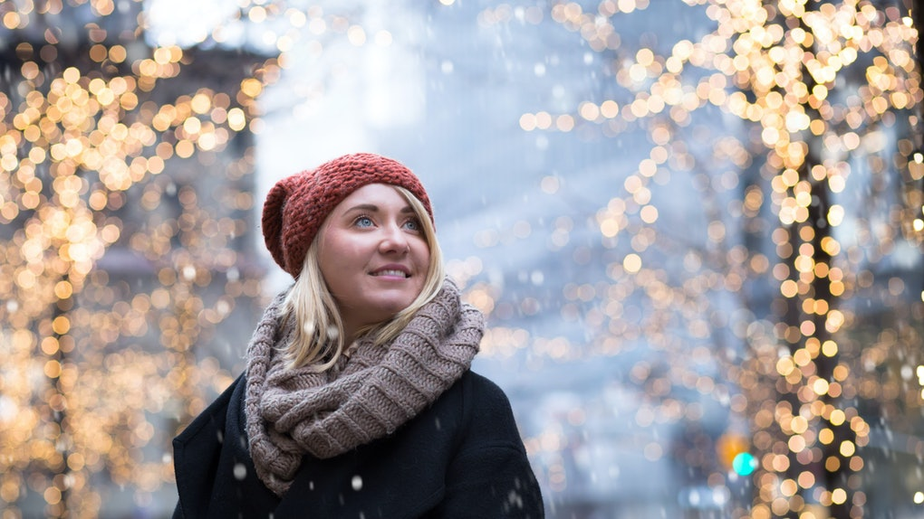 A blonde woman in a beanie cap, scarf, and jacket smiles while snow falls during winter in New York City.