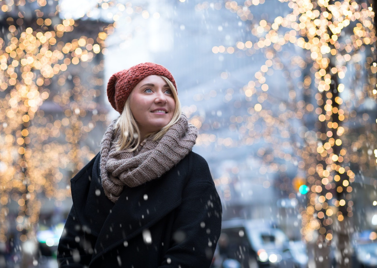 A blonde woman in a beanie cap, scarf, and jacket smiles while snow falls during winter in New York ...