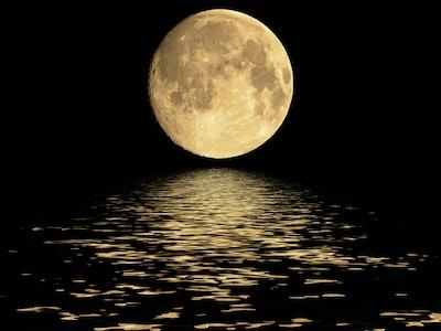 huge full moon on horizon of water, reflecting on black water