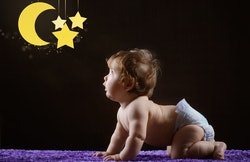 baby on hands and knees, looking at a star and moon mobile