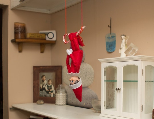 an elf on the shelf doll hanging upside down from a candy cane
