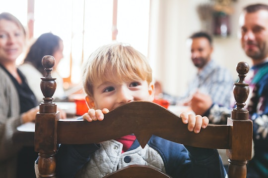 a little boy peeking over the back of a chair at the thanksgiving dinner table
