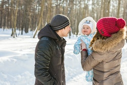 parents with baby outside in snow