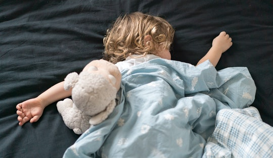 Toddler sleeping in bed with a stuffed lamb