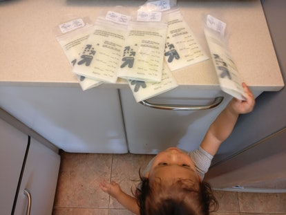 Child reaching for milk bags on bench.