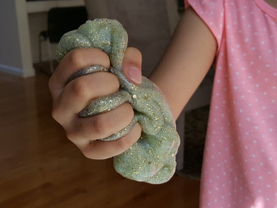 close up of kid holding glittery green slime