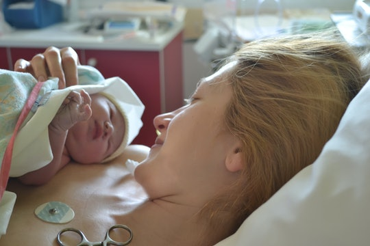 A mom looking down at her newborn on her chest