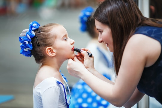 A mom putting lipstick on her young daughter before a dance competition.