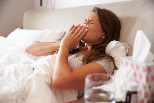 woman laying on back in bed blowing nose really hard with tissues