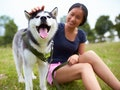 Young woman petting her husky puppy before posting a pic with dog Instagram captions.