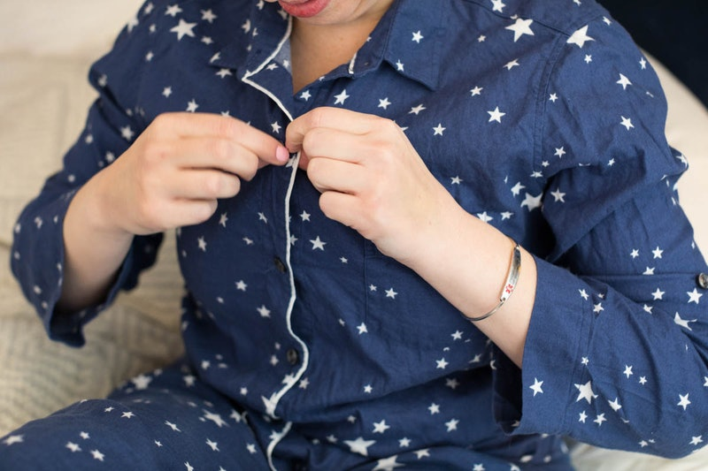 A woman in navy and white pajamas unbuttons her top to do a breast self-exam. What should breast cancer lumps feel like? Doctors explain.