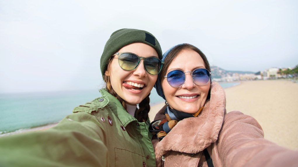 A trendy mom and daughter wearing coats and sunglasses snap a selfie on a beach.