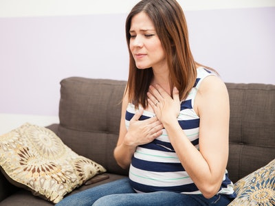 pregnant woman on couch pressing hands against throat and chest in pain