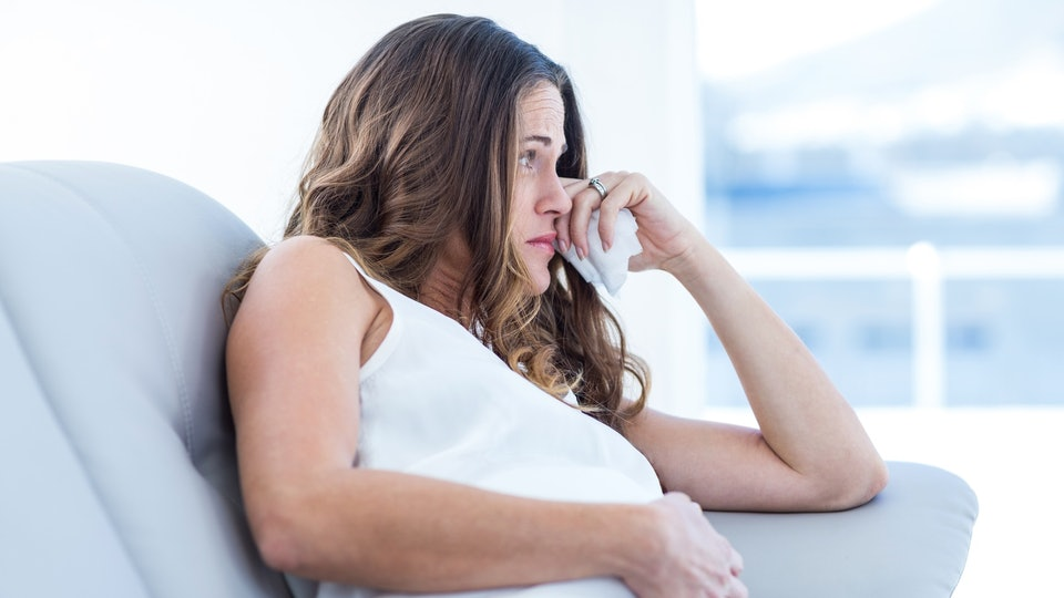 pregnant woman wiping tears holding belly