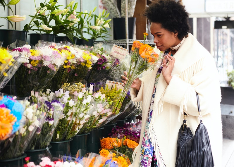 A woman sniffs flowers, remembering her past. Here's how nostalgia can change your brain, according to science and an expert.