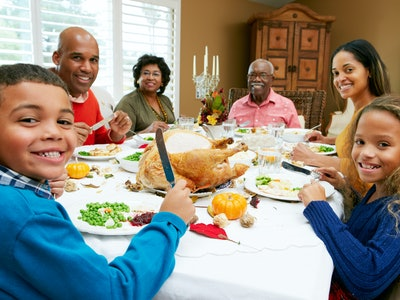 family sitting down at Thanksgiving dinner table