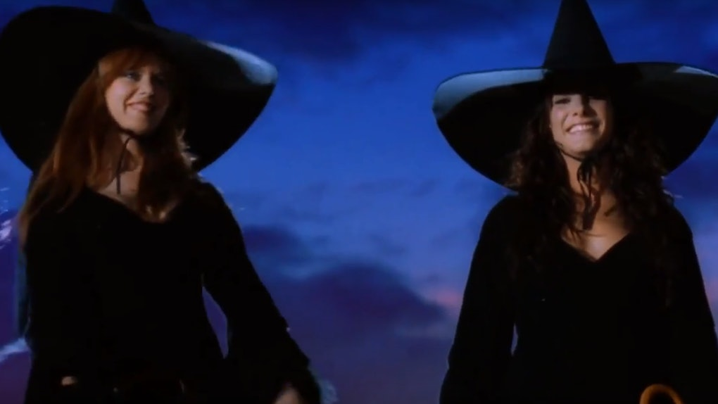 The two witches from 'Practical Magic' smile and fly on their broomsticks in the night.