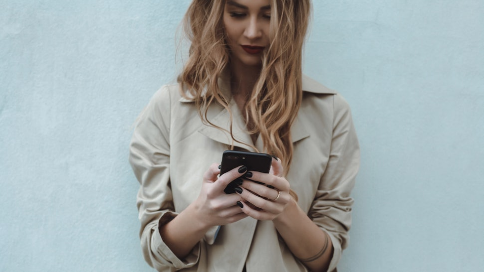 A woman with a phone wondering if Instagram is telling her ex that she just screenshot a photo he posted of himself with his new girlfriend to send to her group chat. Probably.