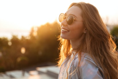 A woman wearing sunglasses outdoors during October, in the golden hour of sunset. October 2021 bring...