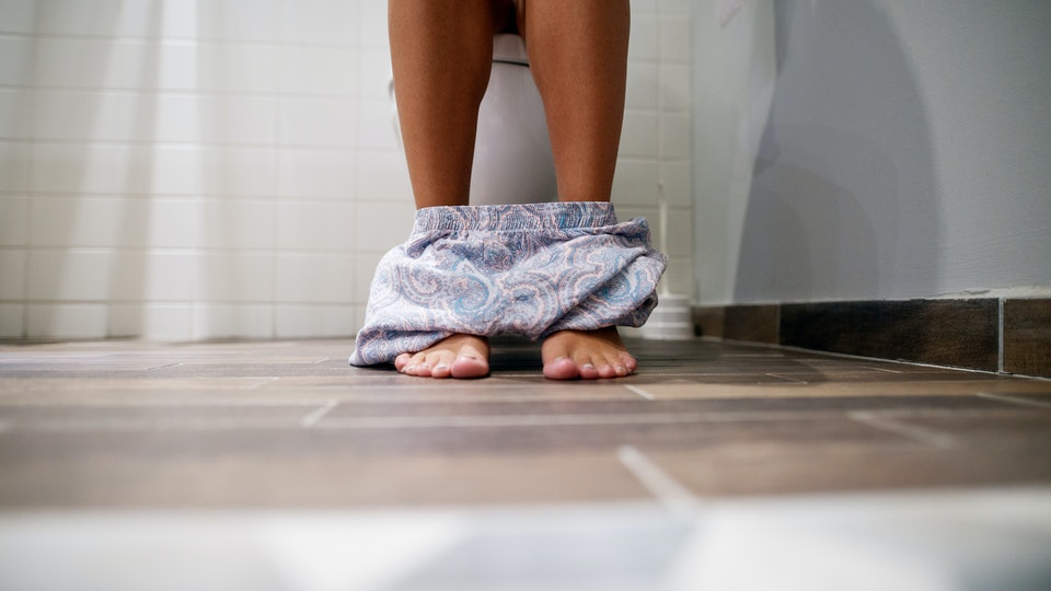 knee down shot of woman on toilet with pants around ankles