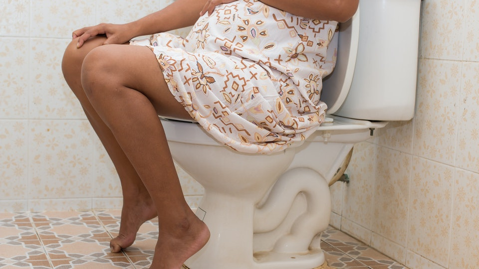 close up of pregnant woman in dress on toilet holding belly