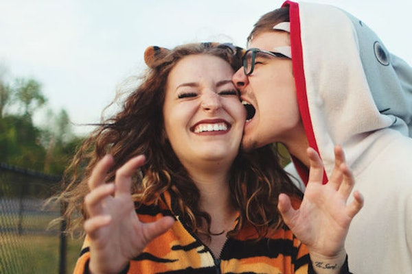 A guy wearing a shark costume kissing a woman wearing a tiger costume on the cheek is perfect for pairing with Instagram captions for couples' Halloween costumes.
