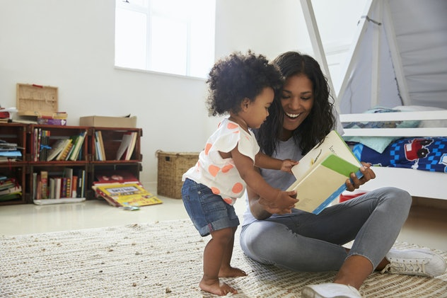 woman and toddler laughing at book in child's room