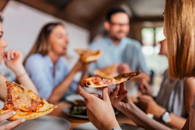 focused shot of person holding slice of pizza among friends at a table