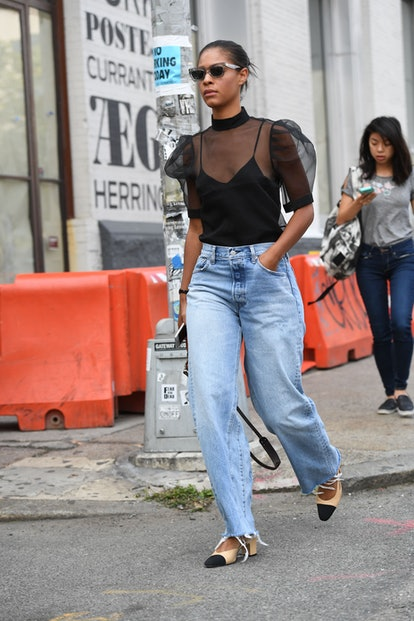 Street style photo featuring an outfit baggy jeans worn with a sheer black blouse that leans into the anti-skinny denim trend.