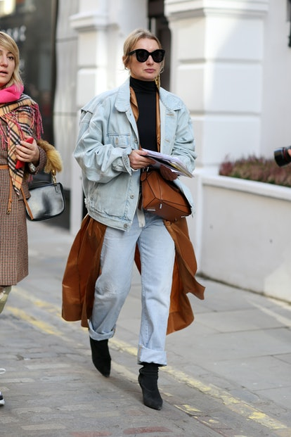 Street style photo of baggy jeans styles with a shirt dress and a denim jacket — an edgier take on Canadian anti-skinny jean tux.