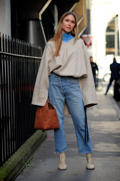 A street style photo featuring an outfit of baggy jeans worn with an oversized wool topper for an ultra-relaxed look.