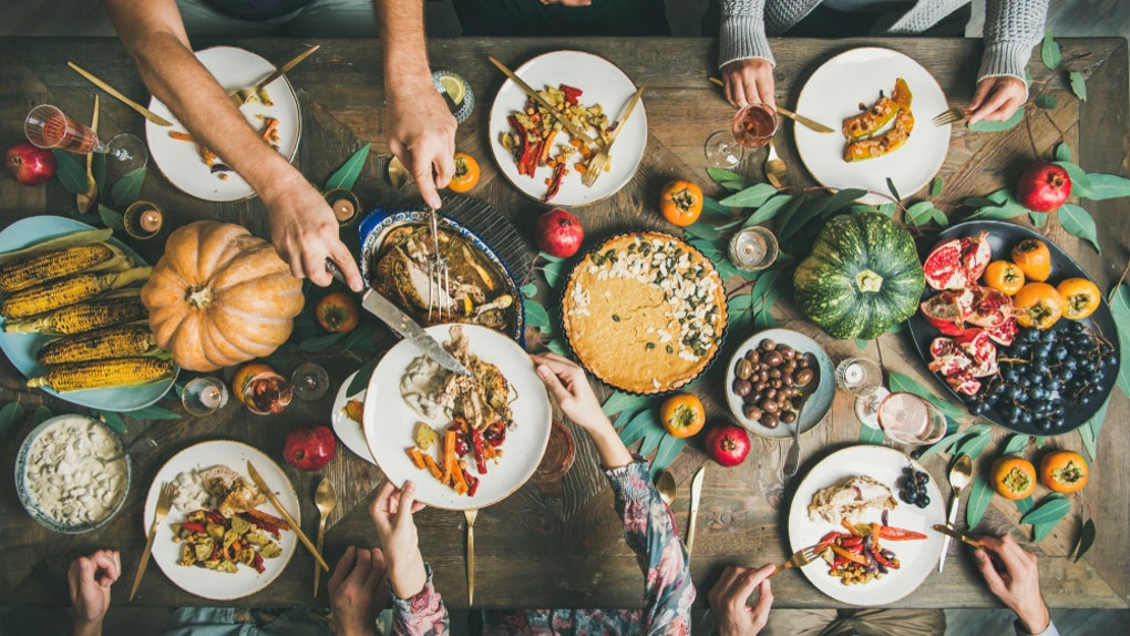 A photo of a large Thanksgiving spread taken from above, while everyone around the table serves themselves and eats from their plates.