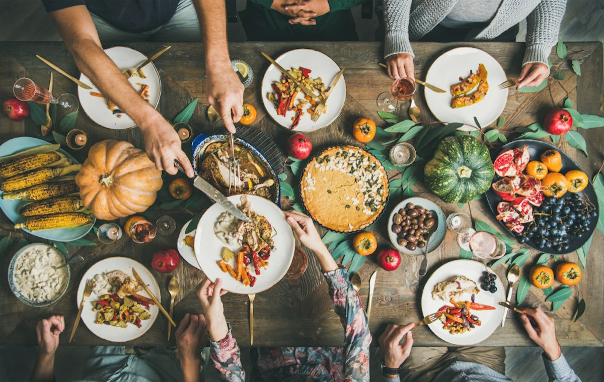 A photo of a large Thanksgiving spread taken from above, while everyone around the table serves them...
