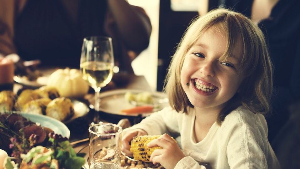 a smiling little girl sitting at the thanksgiving dinner table
