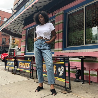 Blogger and model Imani Randolph wears her baggy, anti-skinny jeans with a tied-up white tee and some black mules.