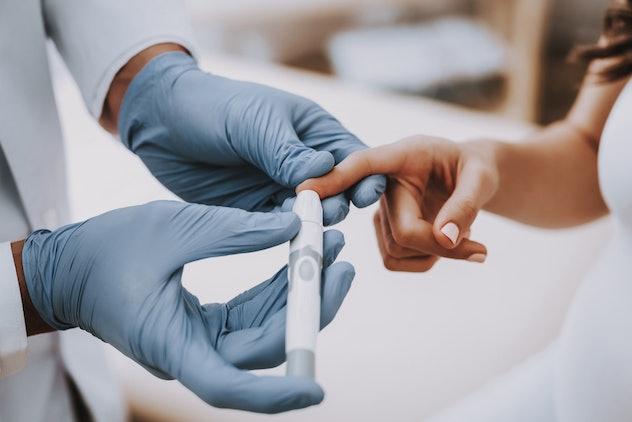 Woman testing blood sugar level
