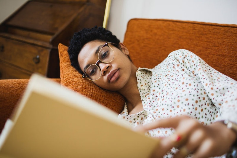 A woman on an orange couch reads a book for self-care, feeling sad that she's missing thanksgiving with loved ones.