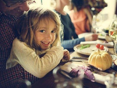 a little girl sitting at the thanksgiving dinner table