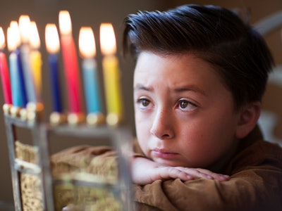 A boy looking at a menorah on Hanukkah