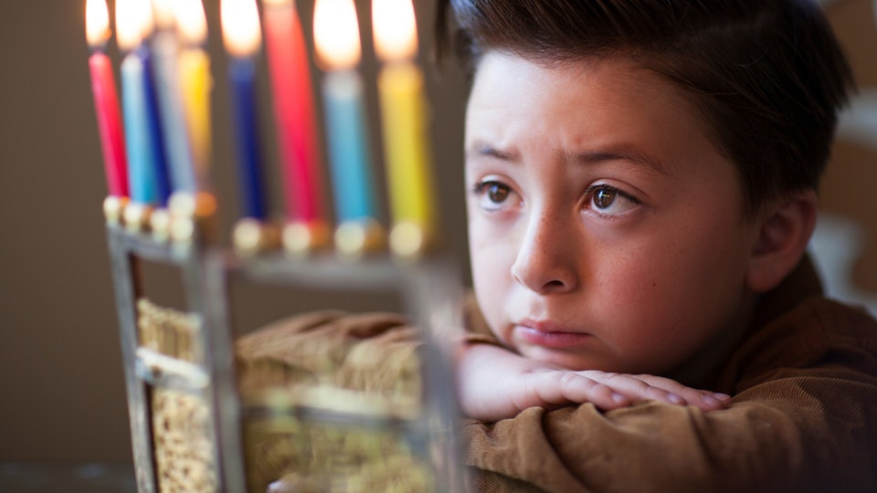 A boy looking at a menorah on Hanukkah