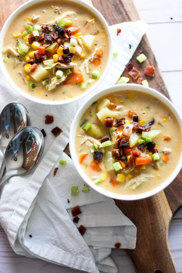 aerial shot of two bowls of light yellow soup with chunks of carrots, celery and potatoes