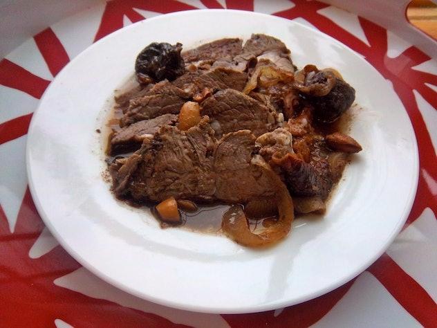 white plate full of sliced lamb covered in prune sauce
