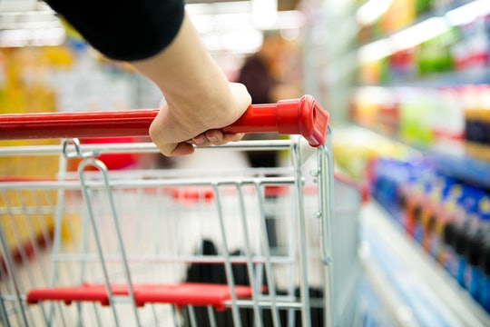 view of a shopping cart going down a grocery store aisle from behind