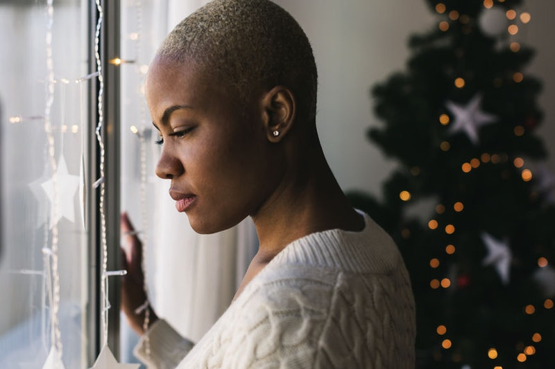 A woman with a shaved head looks out the window at christmas time, coping with grief during the holidays.