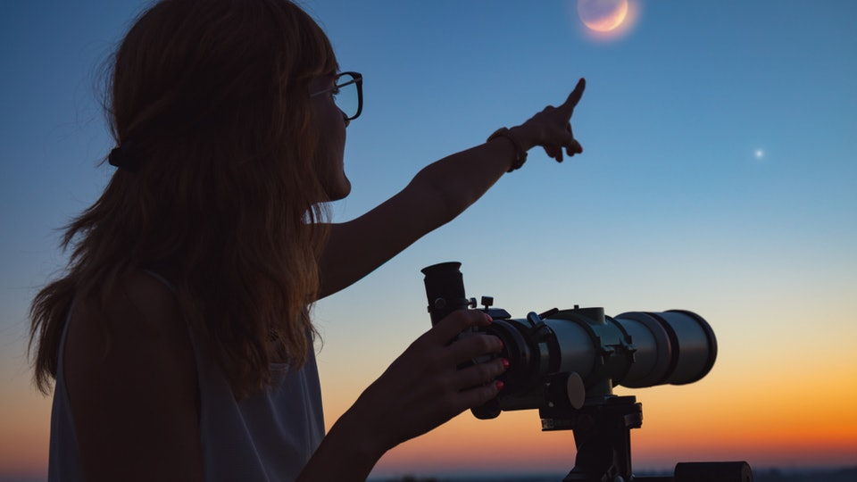 A woman points to the sky, while stargazing with a telescope at sunset.