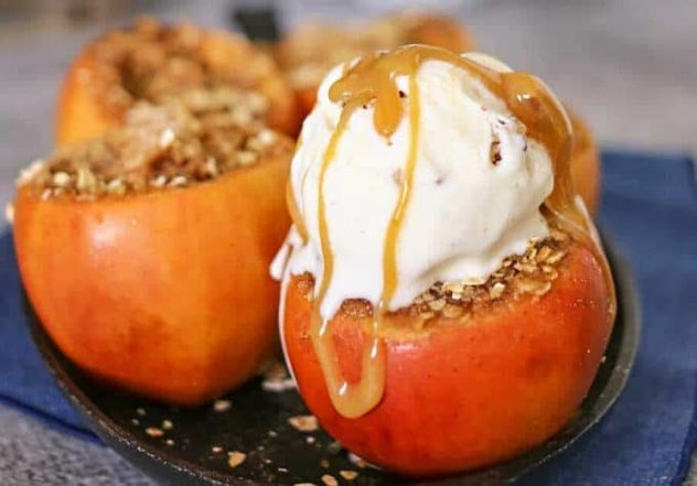 Apples with the top cut off and filled with crushed nuts and ice cream on top drizzled in caramel