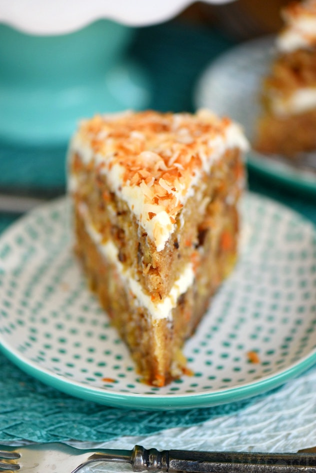 close up of carrot cake with layer of white frosting in middle and on top of cake sprinkled with shredded almonds